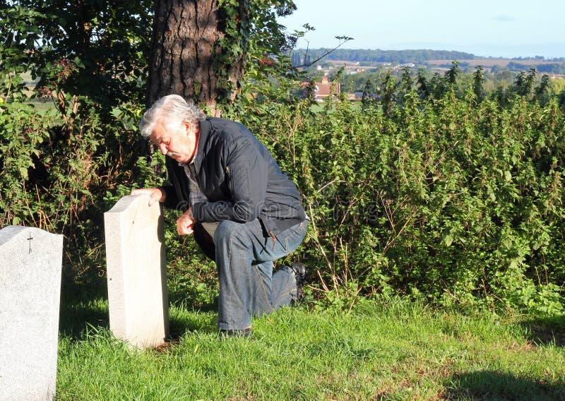 Mens die bij een begraafplaats rouwen. royalty-vrije stock afbeeldingen
