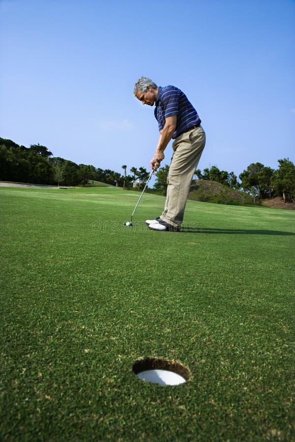 Mens die bij golfcursus zet. stock foto's