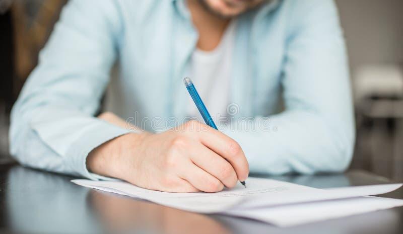 Mens die bij het bureau schrijven stock foto's