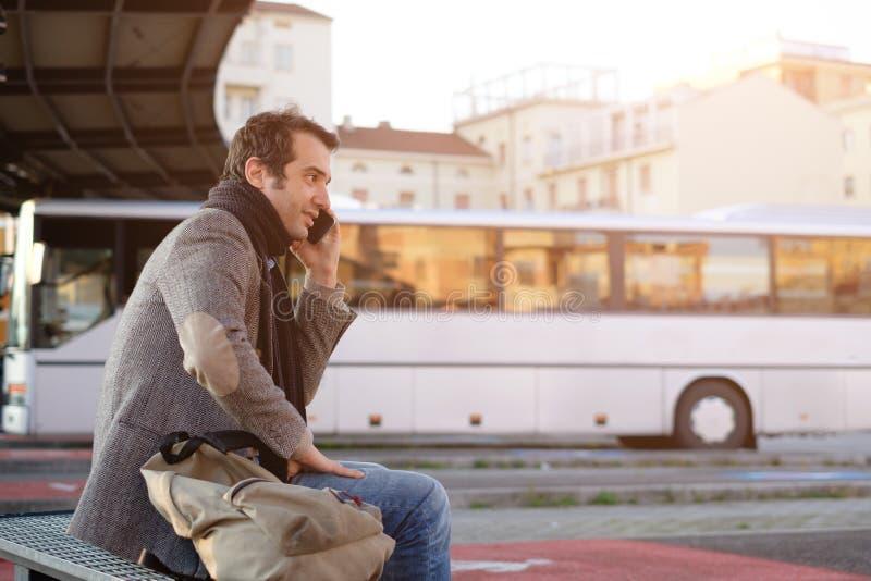 Mens die bij het busstation wachten en op de mobiele telefoon spreken royalty-vrije stock afbeeldingen