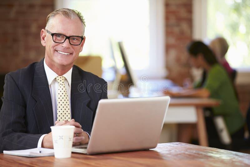 Mens die bij Laptop in Eigentijds Bureau werken stock fotografie