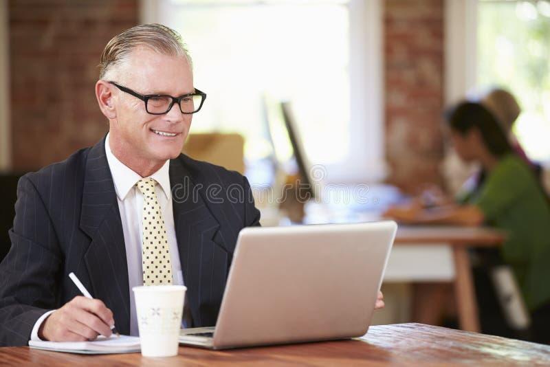 Mens die bij Laptop in Eigentijds Bureau werken stock afbeeldingen
