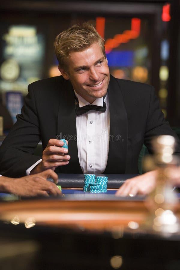 Mens die bij roulettelijst gokt in casino stock foto