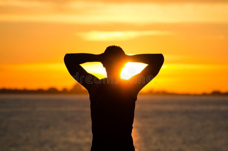 Mens die bij zonsopgang rusten stock fotografie