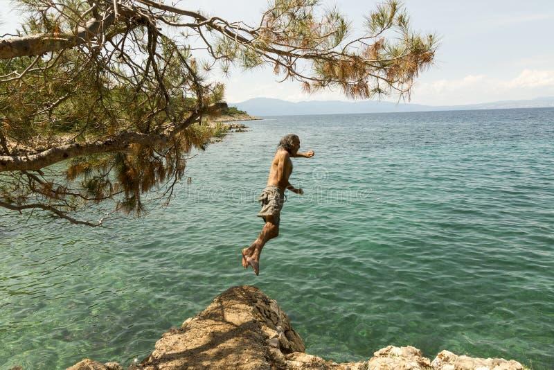 Mens die binnen aan het overzees springen stock foto