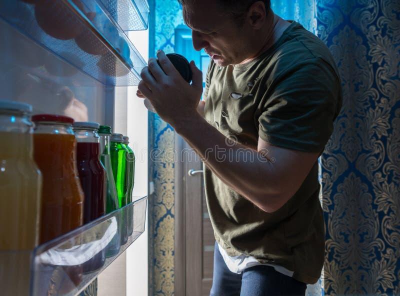 Mens die binnen zijn koelkast bij nacht zoeken royalty-vrije stock afbeeldingen