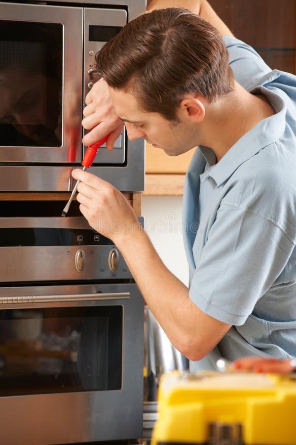 Mens die Binnenlands Oven In Kitchen herstellen stock afbeelding