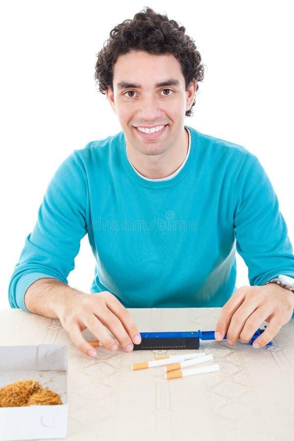 Mens die in blauwe sweater sigaretten met apparaat voor sigaar maken en royalty-vrije stock afbeeldingen