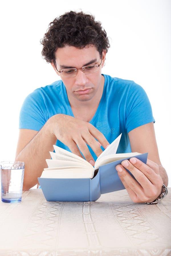 Mens die in blauwe t-shirt met glazen bij lijst en het doorbladeren t zitten stock fotografie