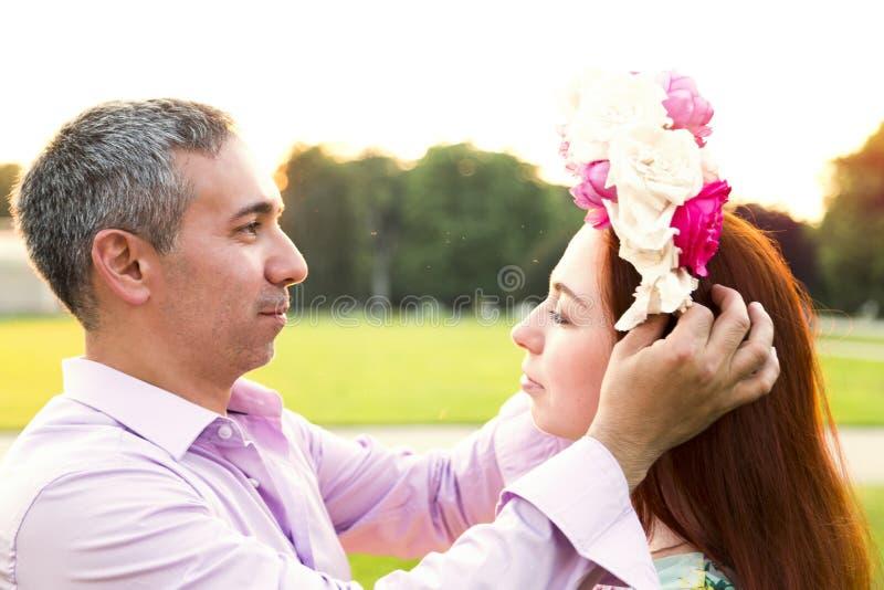 Mens die bloemenkroon op zijn meisjeshoofd zetten stock afbeelding