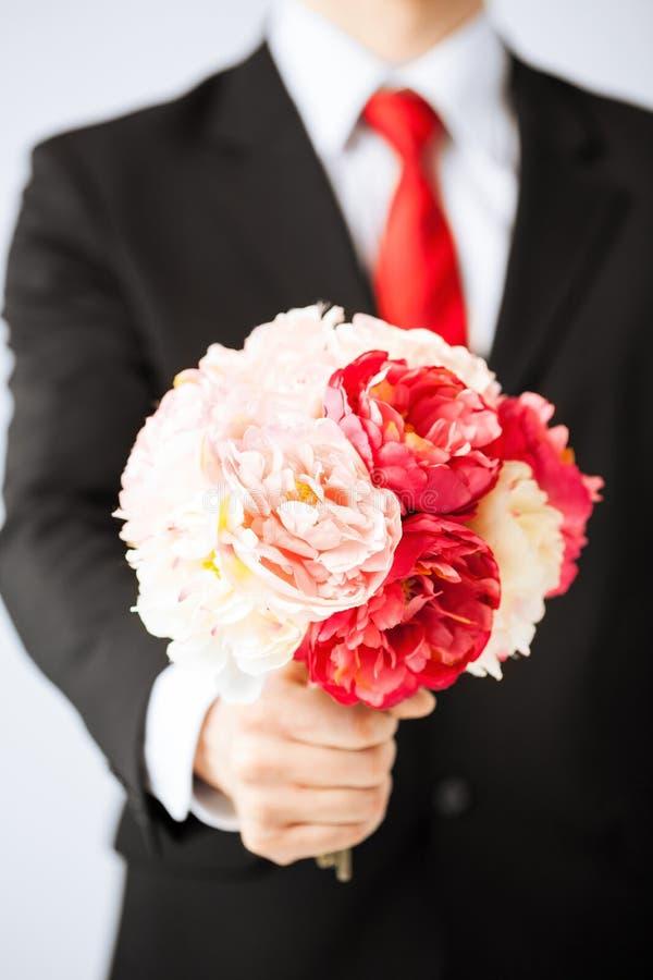 Mens die boeket van bloemen geven royalty-vrije stock foto's