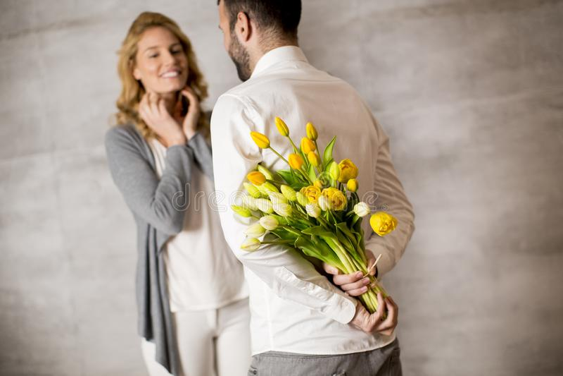 Mens die boeket van gele tulpen geven aan zijn meisje royalty-vrije stock afbeeldingen