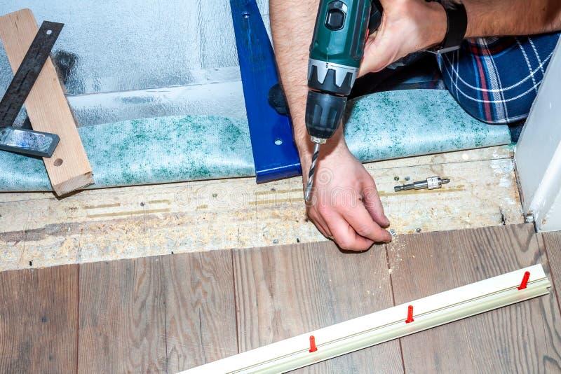 Mens die boormachine met behulp van terwijl thuis het installeren van nieuwe houten gelamineerde bevloering stock foto