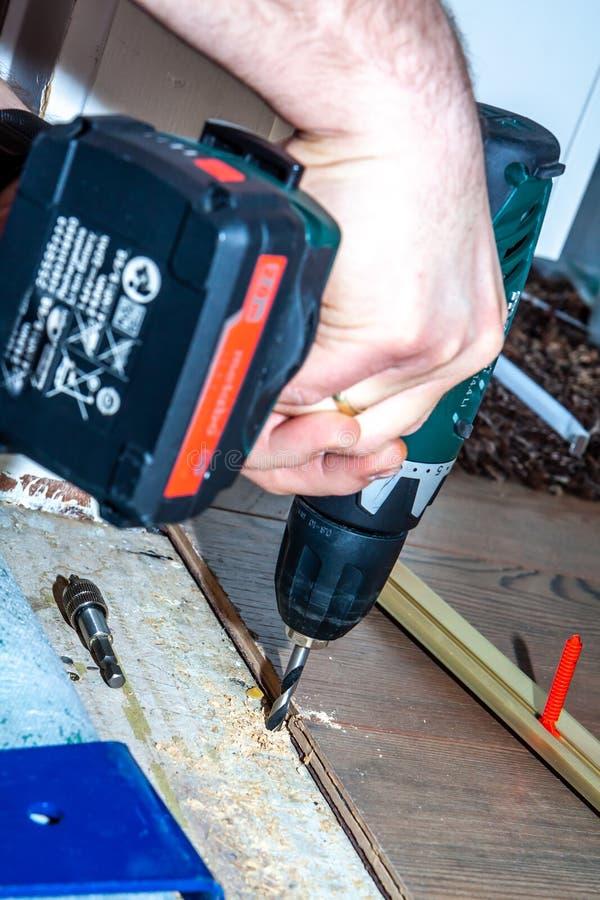 Mens die boormachine met behulp van terwijl thuis het installeren van nieuwe houten gelamineerde bevloering royalty-vrije stock afbeeldingen