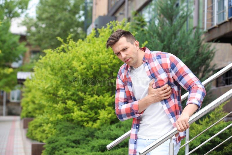Mens die borstpijn hebben in openlucht De mens houdt voor hart stock fotografie