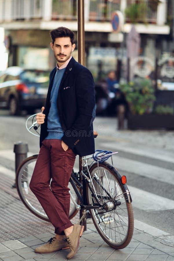 Mens die Brits elegant kostuum in de straat dragen dichtbij oude bycic stock foto's