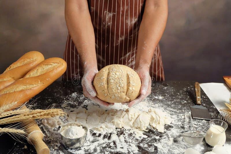 Mens die broodjes voorbereiden bij lijst in bakkerij, Mens die bloem over bestrooien stock afbeeldingen