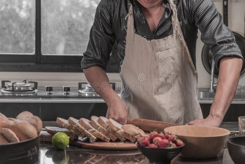 Mens die broodjes voorbereiden bij lijst in bakkerij royalty-vrije stock foto's