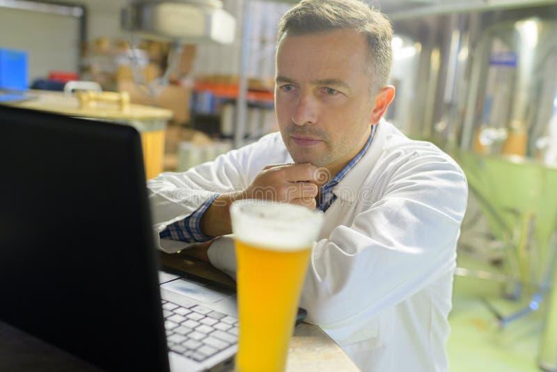 Mens die in brouwerij laptop bekijken stock afbeeldingen