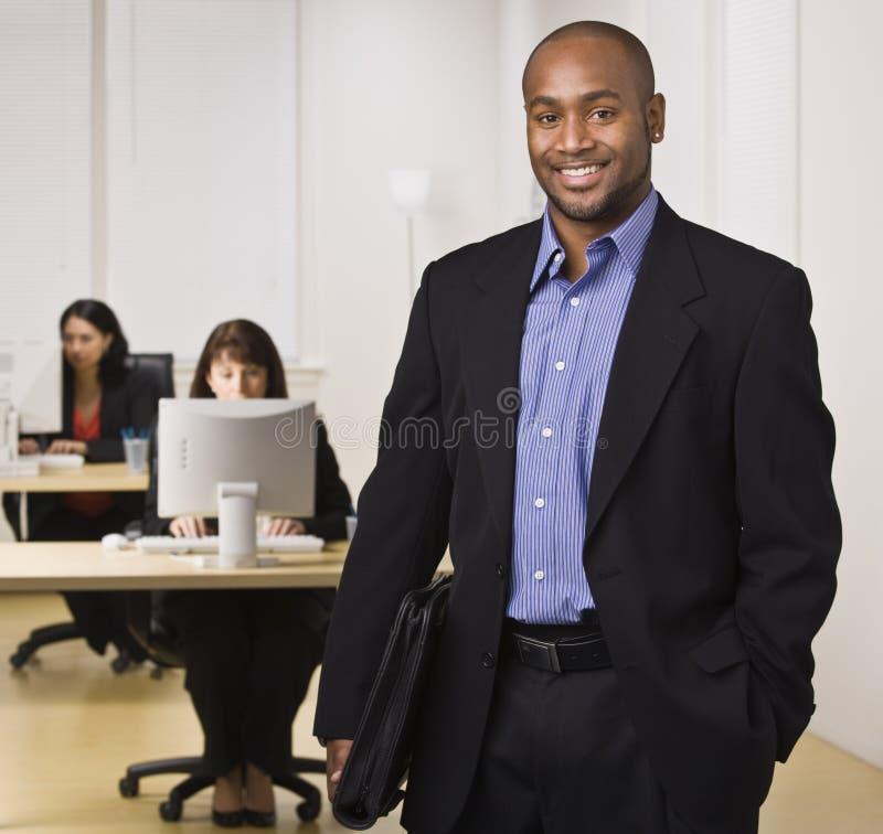 Mens die in Bureau bij Camera glimlacht royalty-vrije stock afbeelding