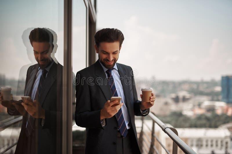 Mens die in bureaukostuum massages controleren op telefoon stock afbeelding