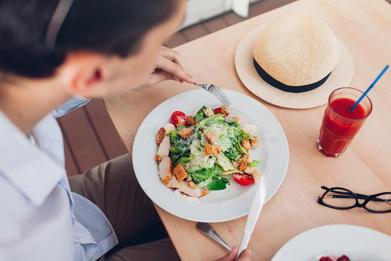 Mens die Caesar-salade eten en tomatesap in restaurant drinken Het hebben van lunch in koffie stock foto's