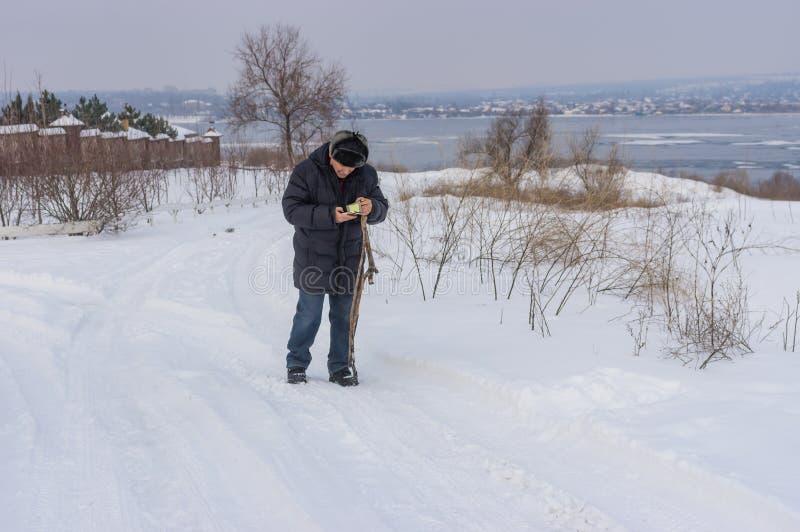 Mens die cellulaire telefoon controleren terwijl het lopen op een sneeuwweg dichtbij bevroren Dnipro rivier in de Oekraïne royalty-vrije stock foto's