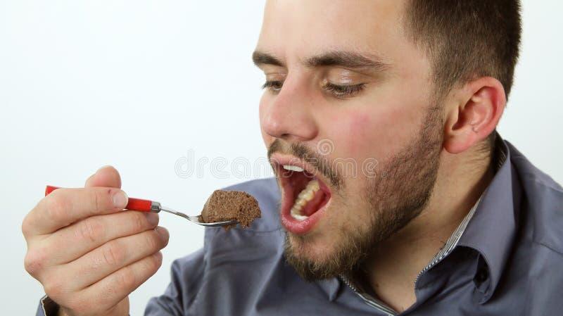 Mens die chocolademousse eten stock foto