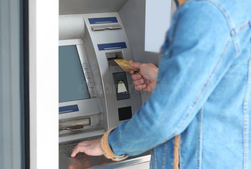 Mens die contant geldmachine voor geldterugtrekking in openlucht met behulp van stock fotografie