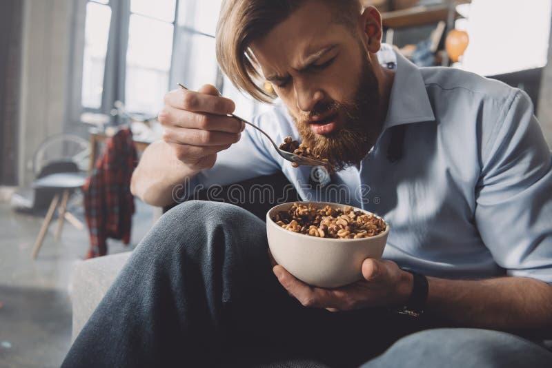 Mens die cornflakes in slordige ruimte eten royalty-vrije stock foto