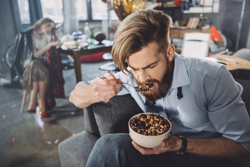 Mens die cornflakes in slordige ruimte eten stock afbeelding