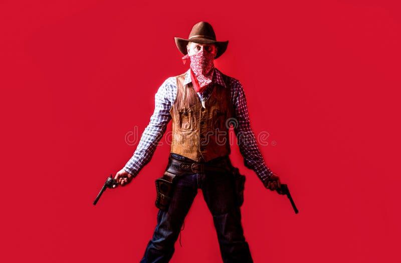 Mens die cowboyhoed, kanon dragen Het westen, kanonnen Portret van een cowboy owboy met wapen op rode achtergrond Amerikaanse ban royalty-vrije stock afbeelding