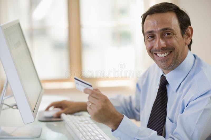 Mens die creditcard en computer met behulp van stock afbeeldingen