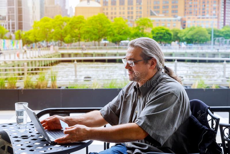 Mens die creditcard en laptop, het winkelen online openlucht met behulp van royalty-vrije stock fotografie