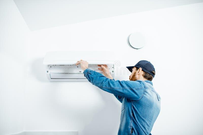 Mens die de airconditioner dienen stock foto's