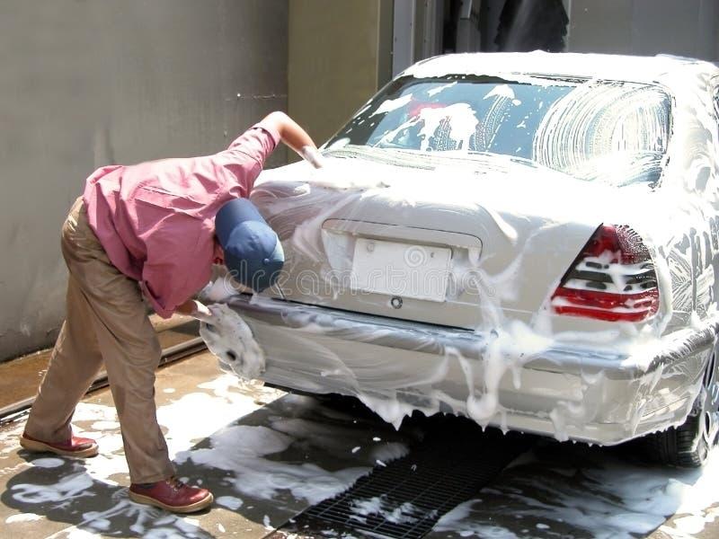 Mens die de auto schoonmaakt stock foto's