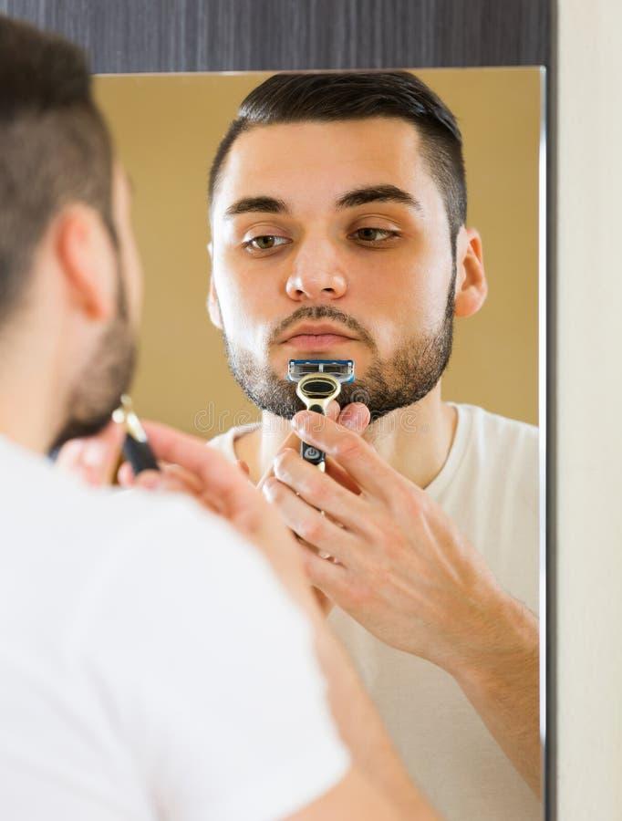 Mens die de baard met een scheermes scheren stock afbeeldingen