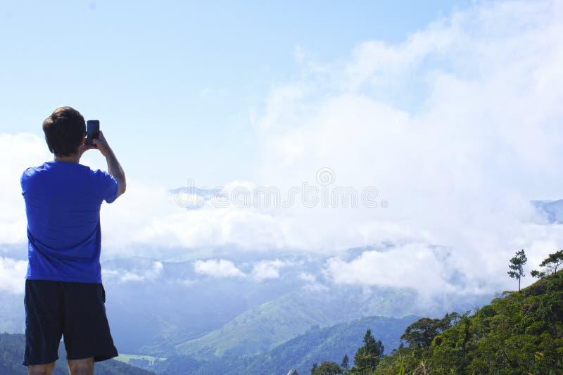 Mens die de bergen fotograferen royalty-vrije stock afbeelding