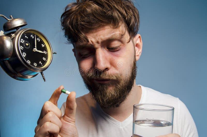 Mens die de blauwe achtergrond van het slapeloosheidsconcept, close-up hebben royalty-vrije stock afbeelding