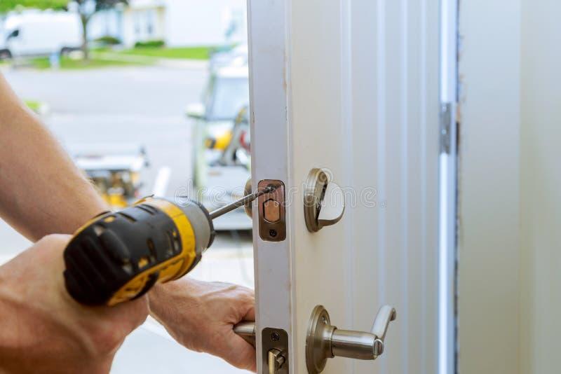mens die de deurknop herstellen close-up van worker& x27; s handen die nieuwe deurkast installeren stock afbeelding