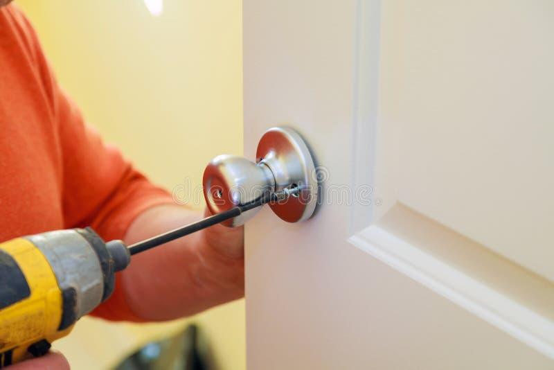 mens die de deurknop herstellen close-up van worker& x27; s handen die nieuwe deurkast installeren royalty-vrije stock afbeeldingen