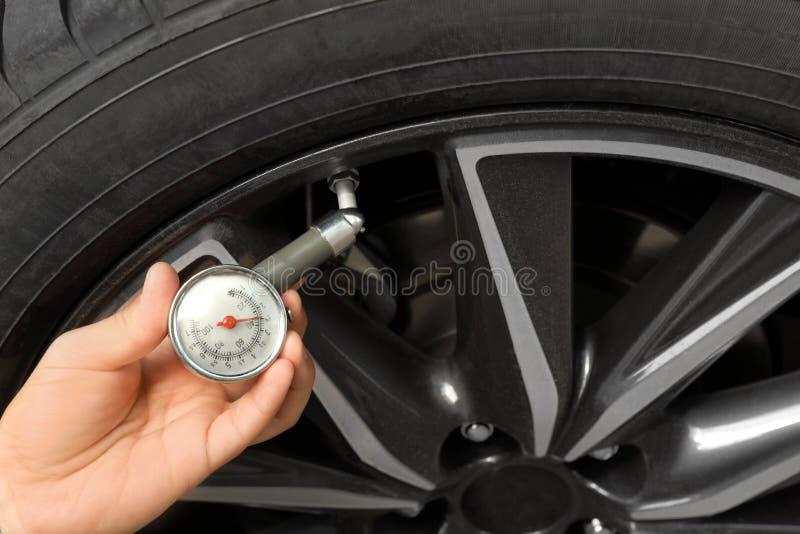 Mens die de druk van de autoband met luchtmaat meten, close-up stock fotografie