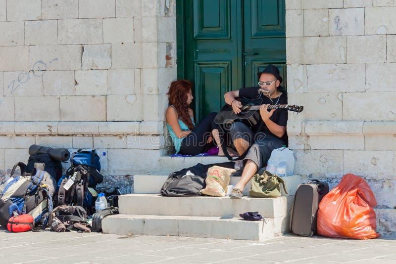 Mens die de gitaar spelen bij de Venetiaanse haven van Chania stock afbeeldingen
