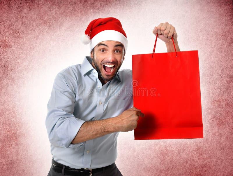 Mens die de holdingskerstmis van de santahoed het winkelen zak gelukkig glimlachen dragen stock fotografie
