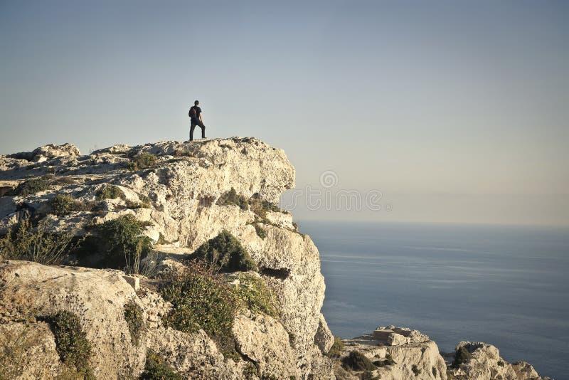 Mens die de horizon van een rots kijkt royalty-vrije stock foto's