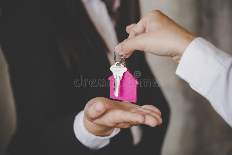 Mens die de huissleutels overhandigen aan een nieuw huis stock afbeelding