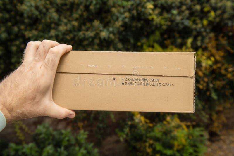 Mens die de kant van het eerste karton van Amazonië houden Japan stock foto