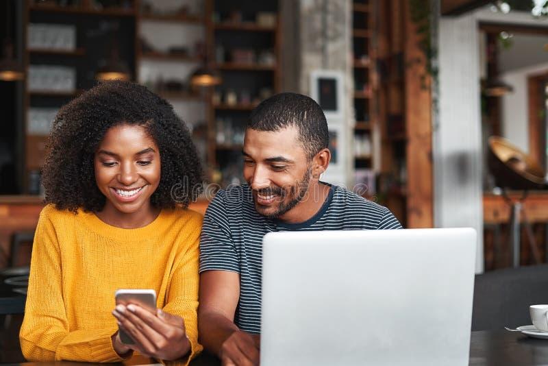 Mens die de mobiele telefoon van zijn meisje in koffie bekijken royalty-vrije stock afbeeldingen