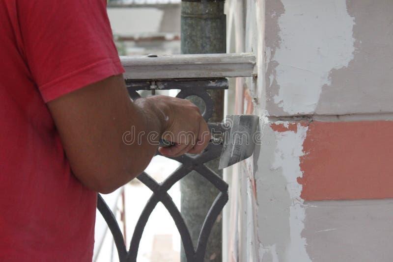 Mens die de muur pleisteren stock foto's