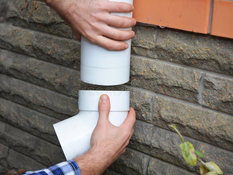 Mens die de plastic pijpleiding van het dakgootsysteem installeren Guttering, Goten, Plastic Guttering, Guttering & Drainage door stock foto